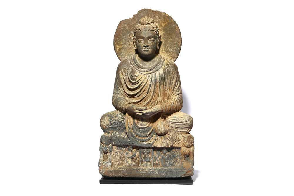 A carved grey schist figure of a seated Buddha