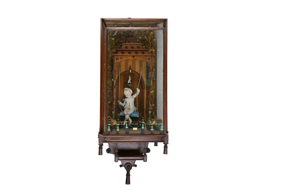 A rare late 19th century automaton in display case depicting a boy on a swing