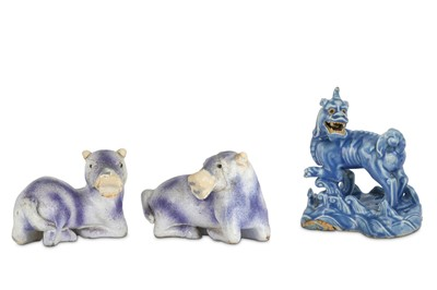 Lot 339 - A CHINESE BLUE-GLAZED BISCUIT MODEL OF A QILIN  AND A PAIR OF PURPLE-GLAZED ANIMALS.