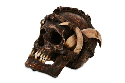 Lot 2-TRIBAL: A DAYAK ANCESTOR HUMAN SKULL DECORATED WITH BOAR TUSKS