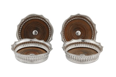 Lot 498 - A set of four George III sterling silver wine coasters, Sheffield 1807 by Samuel Kirby & Co