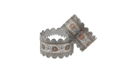 Lot 13-A cased pair of Victorian sterling silver and unmarked gold napkin rings, Birmingham 1885 by Colen Hewer Cheshire