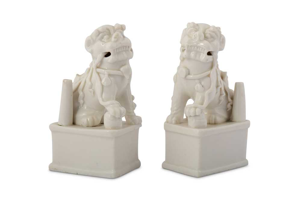Lot 36-A PAIR OF CHINESE BLANC-DE-CHINE LION DOG JOSS STICK HOLDERS.