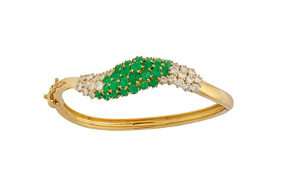 Lot 1241-An emerald and diamond bangle