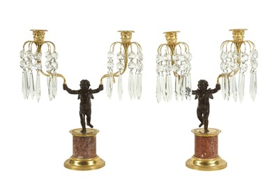 Lot 106 - A PAIR OF EARLY 20TH CENTURY BRONZE AND CUT GLASS FIGURAL CANDELABRA DEPICTING CUPID